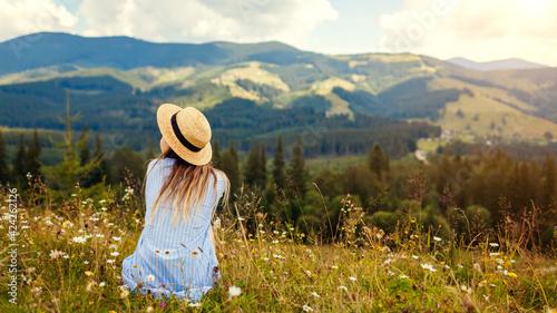 Obraz Traveling in spring Ukraine. Trip to Carpathian mountains. Woman traveler relaxing in flowers admiring landscape view - fototapety do salonu