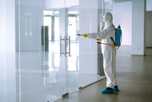Man In Hazmat Suit, Protective Gloves And Goggles Use Sprayer Equipment Disinfect  In Office. Protection Agsinst COVID-19 Disease.