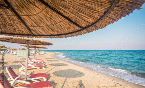 Fotografia Straw umbrella and sunbeds on Marmari beach, Kos, Greece