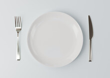 Mockup White Plate On A White Table. Mockup  Two White Plates With A Silver Fork And A Knife On The Table. Small And Large White Plate With A Knife And Fork. 3D Concept. 3d Illustration