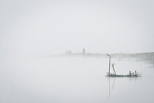 Morning River Before Dawn. Thick Fog Tightened The Whole Shore. Through The Fog You Can See The Silhouettes Of Fishermen.