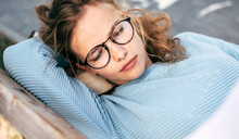 Gorgeous Female In Blue Sweater, Eyeglasses, Takes A Rest On The Bench Outside. Young Woman Sleeping Outdoors.