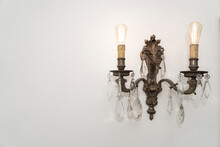 Old Row Chandelier Hanging On A White Wall. Lamps On.