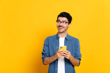 Joyful Happy Good Looking Stylish Caucasian Unshaven Guy Holding Smartphone In Hand, Chatting Online, Browsing Internet, Looking Happily To The Side, Standing Against Isolated Orange Background, Smile