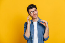 Phone Call By Cellphone. Attractive Charismatic Stylish Guy Has An Unpleasant Phone Conversation, Ignores The Interlocutor, Makes Blah Blah Gesture, Stands On Isolated Orange Background, Looks Away