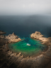 Aerial View Of A Motor Boat Anchored In A Small Bay With Rock Formation Along The Coastline At La Maddalena Island, Sassary, Italy.