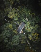 Aerial View Of A Pick-up Vehicle Driving A Beautiful Road Among The Deep Forest Vegetation Crossing A Small Stream On Pico Island, Azores Archipelagos, Portugal.