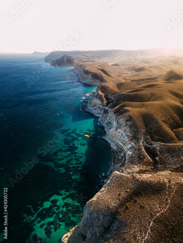 Aerial view of beautiful coastline with cliffs and turquoise water near Almeria, Andalusia region, Spain.