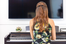 Rear View Of Beautiful Woman In Dress Playing Piano In Living Room, Young Girl Playing Grand Piano At Home