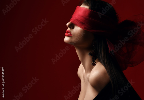 Profile of excited woman with naked shoulders and breast holds and eyes covered with red scarf, blindfold over dark background with copy space. Fashion, vogue, sexy stylish look for woman concept