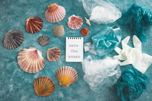 Save The Ocean Text On Blue Bakground With Sea Shells And Plastic Garbage Symbol Of Environmental Pollution To Fix, Ecology And Respect For The Planet
