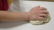 Hands kneading dough on sprinkled with flour table closeup