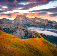 Breathtaking Autumn View From The Top Of Rolle Pass. Fantastic Morning Scene Of Dolomites. Foggy Landscape Of Mountain Valley, Trentino Province, Italy, Europe. Traveling Concept Background.