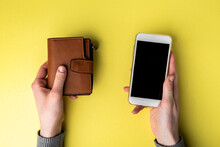 Brown Leather Wallet And Mobile Phone On Yellow Background.