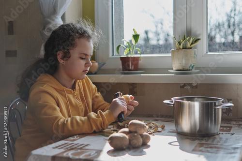 Fototapeta DZiewczynka obierajaca ziemniaki do obiadu obraz