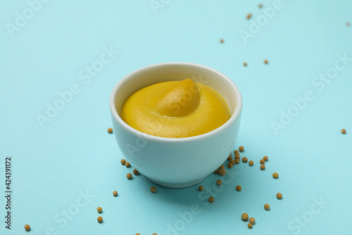 Fototapeta Bowl with mustard and seeds on blue background obraz