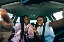 Two African Woman Making Selfie In Auto.Woman Sitting Inside, Smiling, One Woman Holding Phone. Female Customers Happy Because Of Purchasing New Auto.