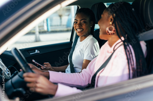 Obraz Two beautiful and pretty african women driving in car of their dream. Two women smiling because of successful purchase of automobile in car dealership. - fototapety do salonu