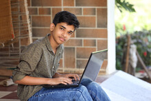Portrait Of Indian Boy Using Laptop While Attending The Online Classes At Home