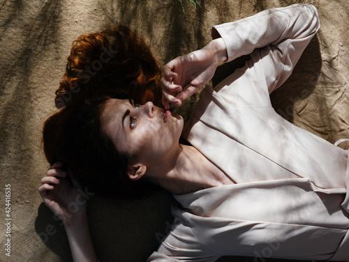Obraz Pretty woman is lying on the ground sand resting tropics fresh air - fototapety do salonu