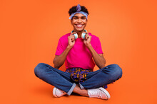 Full Length Body Size Photo Of Happy Young Man Wearing Wireless Headphones Smiling Sitting Down Isolated Vibrant Orange Color Background