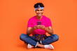 Full length body size photo of young hipster browsing internet with smartphone smiling isolated bright orange color background