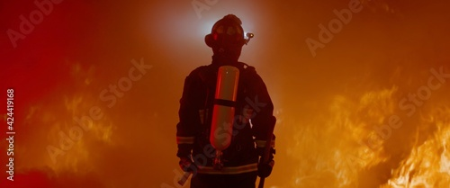 Canvas Print Dramatic silhouette of American firefighter in full gear exploring the huge fire