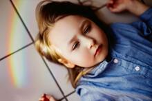 Rainbow Reflection On The Face Of A Little Girl Lying On The Floor