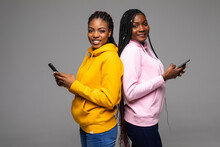 Portrait Of Young African Women With Mobile Phone Back To Back Each Other Isolated On Gray Background