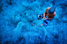 Old Fisherman Hands Sewing Blue Fishing Nets Sitting On The Ground And Surrounded Big Net