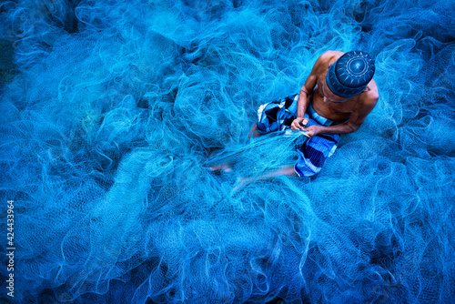 Fototapeta Old fisherman hands sewing blue fishing nets sitting on the ground and surrounde