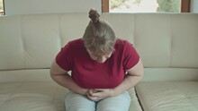 Portrait Of A Caucasian Woman With Blonde Hair Sitting On Sofa Having Strong Stomach Ache Hands On Abdomen