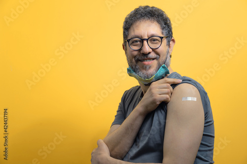 Fotografering Handsome fifty years old man with lowered face mask showing arm with bandage after the coronavirus vaccination looking at the camera against an orange background