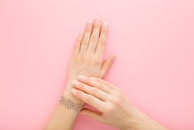 Bracelet Of Small Gems On Young Adult Woman Wrist On Light Pink Table Background. Pastel Color. Beautiful Groomed Hands. Soft Touch. Closeup. Point Of View Shot. Top Down View.