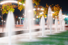 Autumn City Park At Night, Fountains, Trees With Yellow Leaves And Street Lights