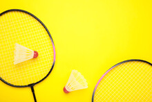 Shuttlecocks And Badminton Rackets On Yellow Background. Badminton Equipment