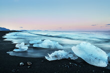 Ice Floe In The Water By The Ocean At Sunrise. Glacial Lagoon. Iceland. Long Exposure With Blurry Water.