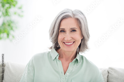 Obraz Photo of attractive positive old woman smile good mood wear casual clothes indoors inside house apartment - fototapety do salonu