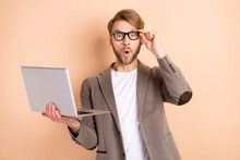 Photo Of Impressed Nice Blond Hair Man Hold Laptop Wear Spectacles Grey Jacket Isolated On Beige Background