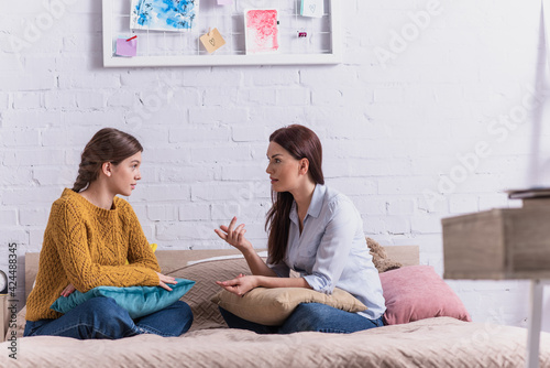 Obraz mother gesturing while talking with teenage daughter in bedroom - fototapety do salonu