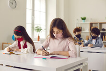 Students Cover Mouths And Noses At School During Global Coronavirus Pandemic. Two Little Girls Wearing Handmade Face Masks In Classroom. Focused Young Children Writing Essays Sitting At Desk In Class