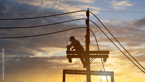 Fototapeta silhouette electricians work on high voltage towers to install new wires and equipment. obraz