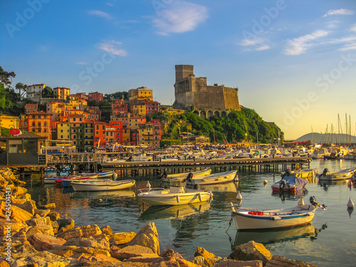 Fotografie, Obraz Lerici , Italy- June 5, 2010: San Giorgio castle of Lerici town from the of Gulf of Poets with sailing boats and motor boats at sunset