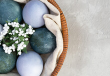 Easter Eggs In A Basket With Artificial Flowers Are Painted With Natural Dyes. Hibiscus Tea And Red Cabbage