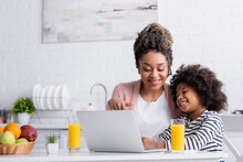 Smiling African American Woman Pointing At Laptop While Watching Movie With Daughter In Kitchen