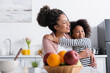 canvas print picture cheerful african american woman and child embracing while looking away near fruits on blurred foreground