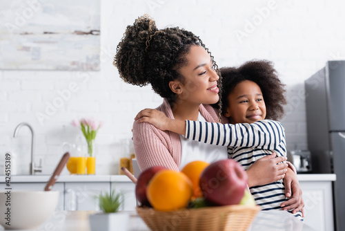Photo cheerful african american woman and child embracing while looking away near frui