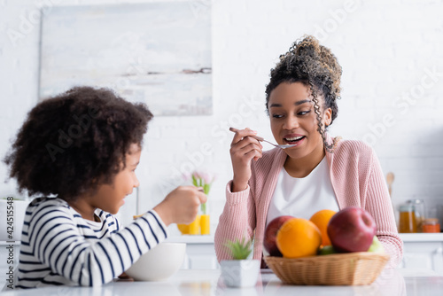 Fotografie, Tablou cheerful african american woman looking at daughter while holding spoon with cor