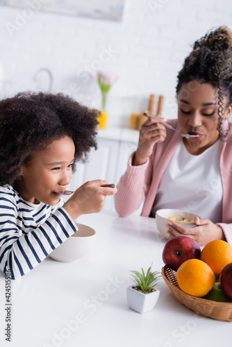Fototapeta african american mother and daughter eating tasty corn flakes for breakfast obraz