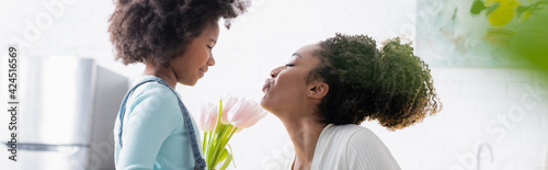 Obraz na plátně side view of african american woman blowing air kiss to smiling daughter with fr